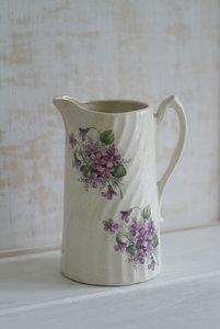 Kan met lila bloemen